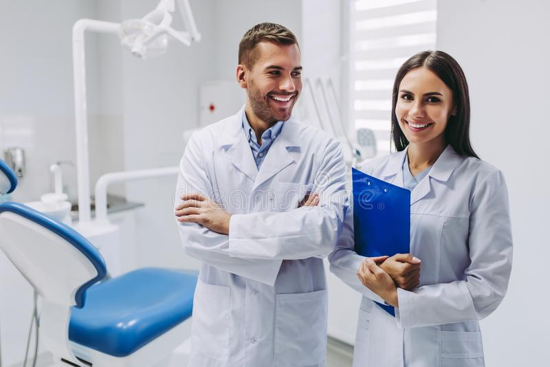 Dentists at workplace in dental clinic. Smiling dentists looking at the camera standing at workplace in modern dental clinic stock image