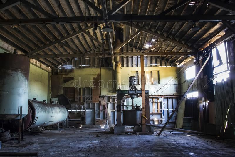 Dentro da construção velha da fábrica de conservas com equipamento oxidado e teto e paredes de madeira de desintegração foto de stock royalty free