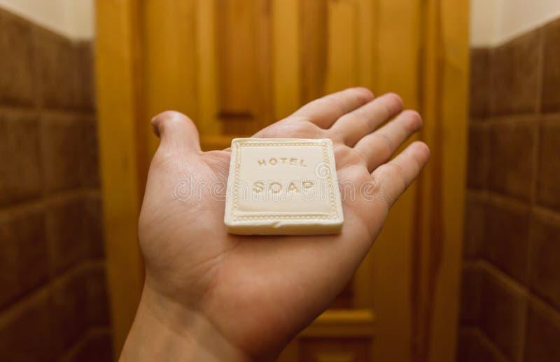 Dentro da sala de hotel, uma mão de um visitante que guarda a parte pequena de banha arti'culos de tocador do frjm do sabão em um imagens de stock