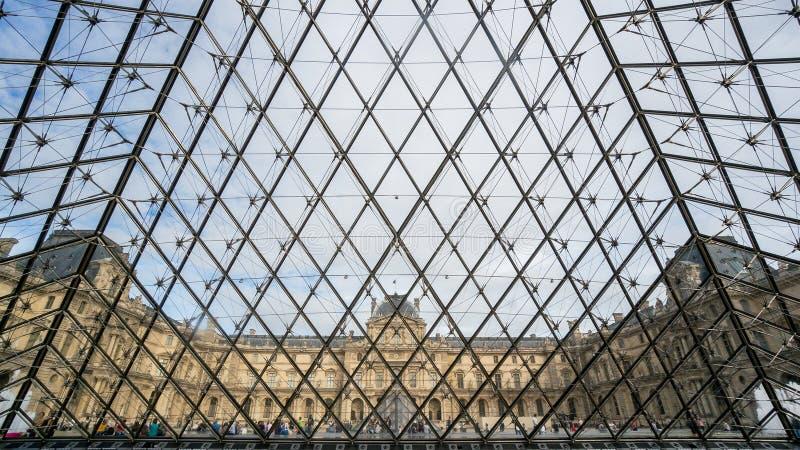 Dentro de la pirámide cristalina del museo del Louvre en París fotos de archivo