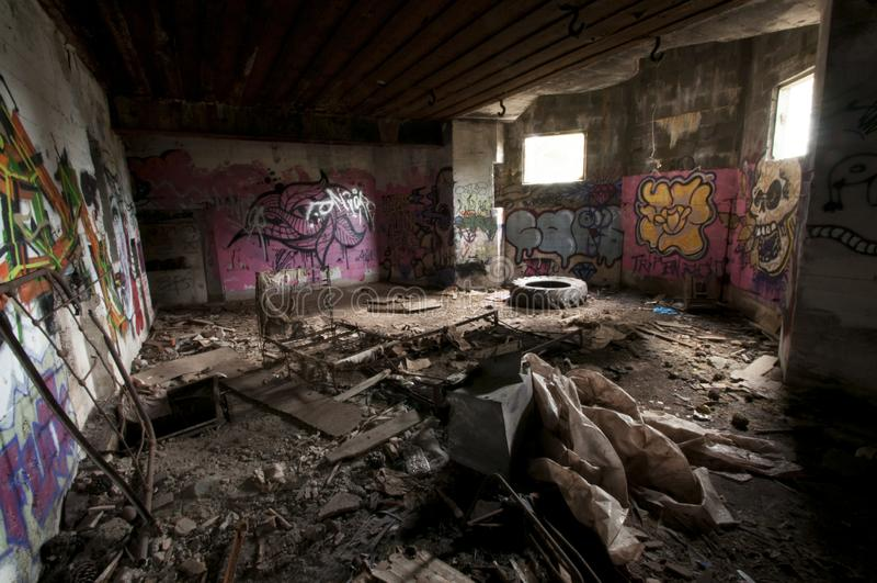 Dentro de um casemate concreto abandonado de WWII com grafittis e do esqueleto de uma cama metálica na costa atlântica francesa foto de stock