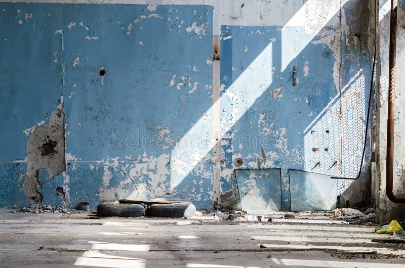 Dentro de uma construção industrial abandonada velha, fábrica A parede com descascamento da pintura azul Pneus usados, rodas Muit imagens de stock