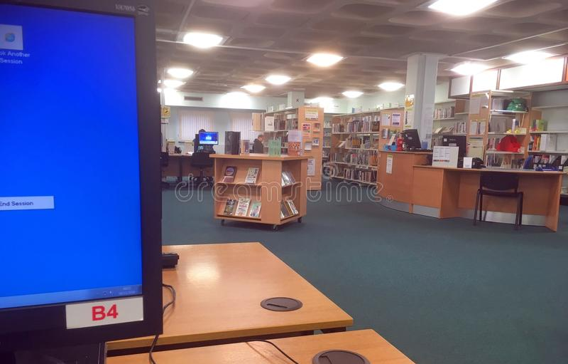 Dentro de una biblioteca pública con el ordenador y los libros fotos de archivo