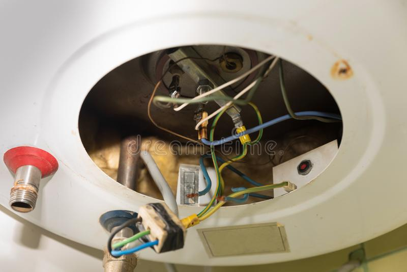 Dentro del calentador o de la caldera quebrado de agua con los alambres y los tubos eléctricos para la instalación de las manguer fotografía de archivo