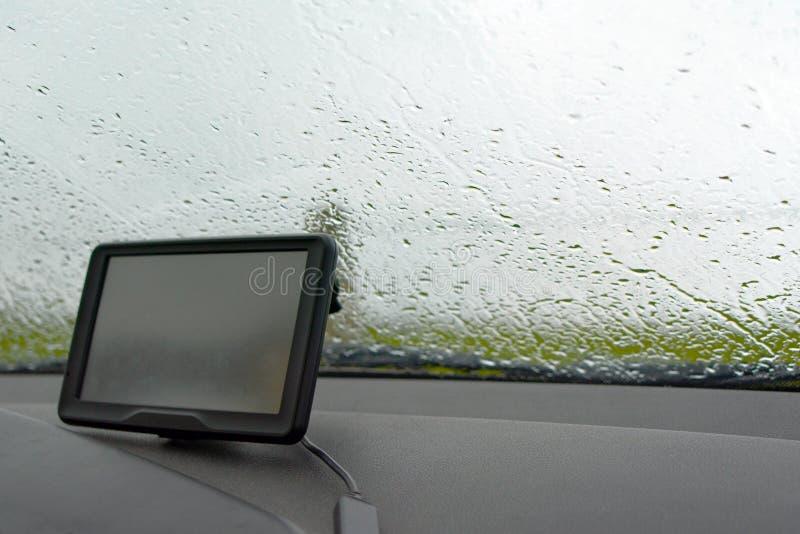 Dentro di un'automobile con pioggia sulla finestra del parabrezza e sul sistema di navigazione di GPS in maltempo immagine stock libera da diritti