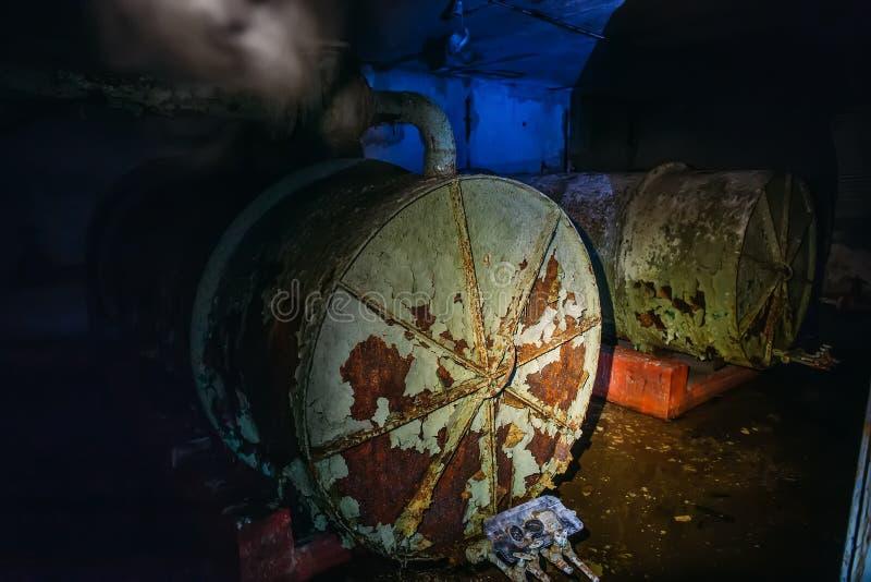 Dentro do depósito soviético abandonado velho, sala escura com os tanques redondos de aço grandes fotos de stock royalty free