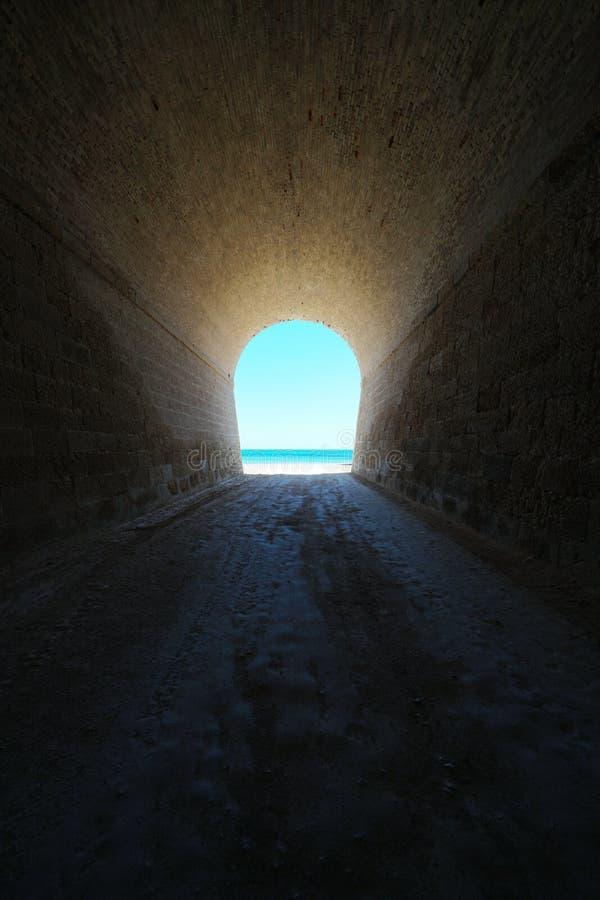 Dentro il tunnel che conduce alla scena naturale della spiaggia fotografia stock