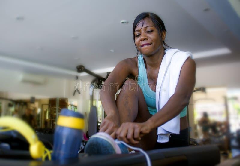 Dentro retrato del entrenamiento afroamericano negro atractivo y feliz joven de la mujer en el gimnasio que ata las zapatillas de fotos de archivo