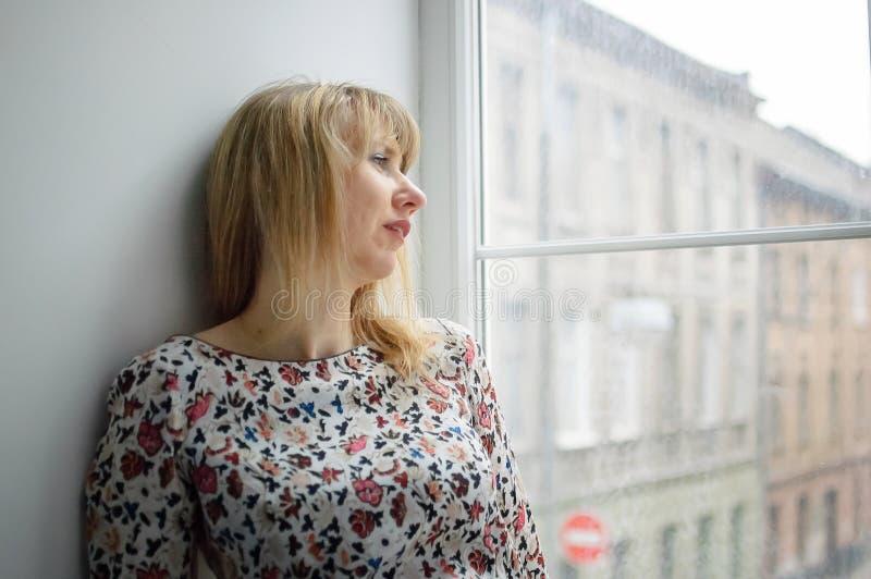 Dentro retrato femenino de una mujer envejecida media hermosa que lleva el vestido caliente y que se coloca al lado de ventana en fotos de archivo libres de regalías
