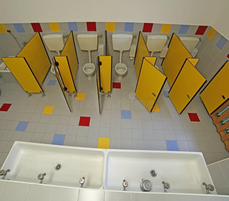 Dentro un bagno di una scuola materna con le piccole toilette fotografie stock