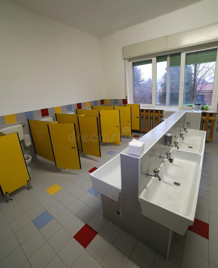 Dentro un bagno di una scuola materna con le piccoli toilette e peccato immagine stock