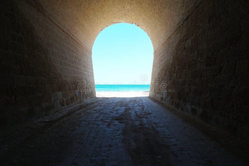 Dentro un tunnel conduce alla scena naturale della riva di mare immagini stock libere da diritti