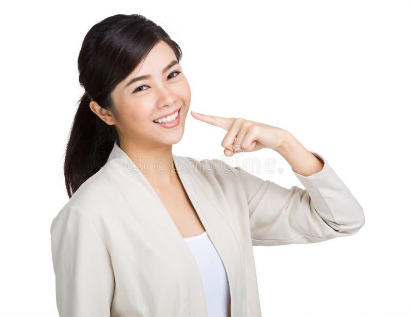 Dents blanches d'exposition heureuse de femme avec le doigt photographie stock libre de droits