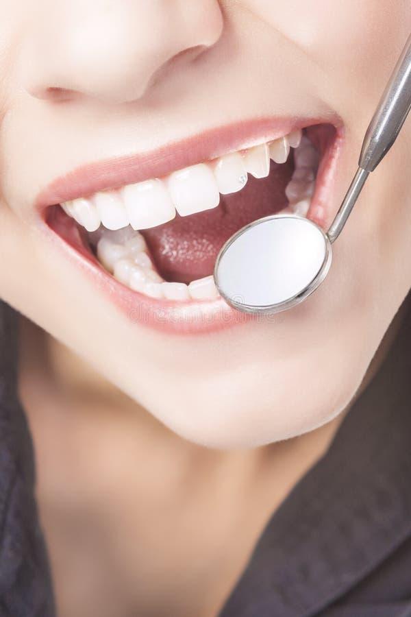 Dents blanches de femme caucasienne avec le dentiste Mouth Mirror image libre de droits
