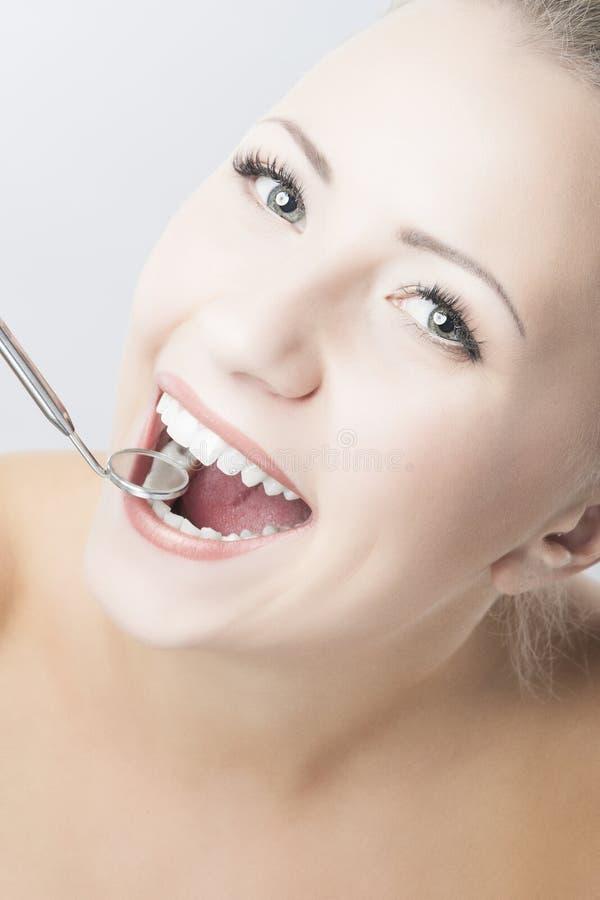 Dents caucasiennes de femme avec le miroir dentaire image libre de droits