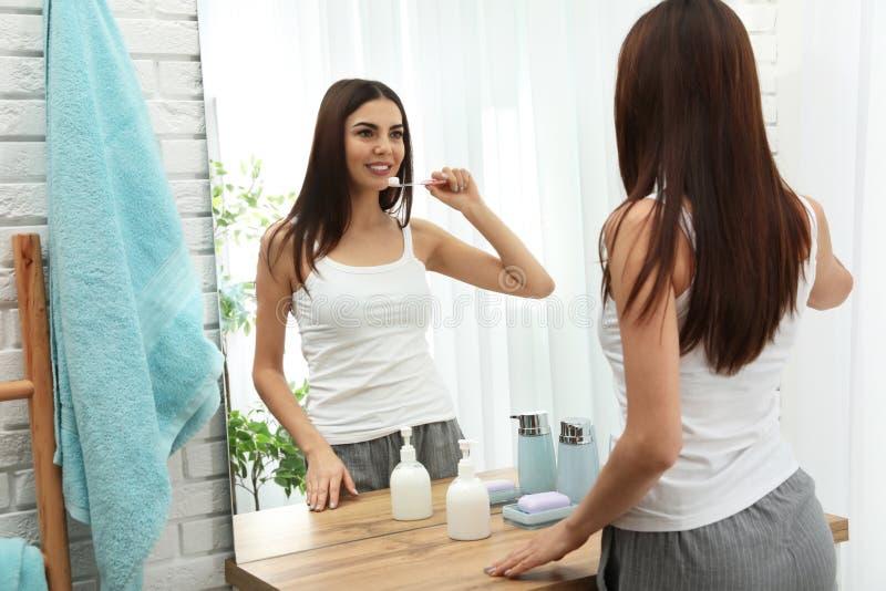 Dents de brossage de belle femme près de miroir dans la salle de bains images stock