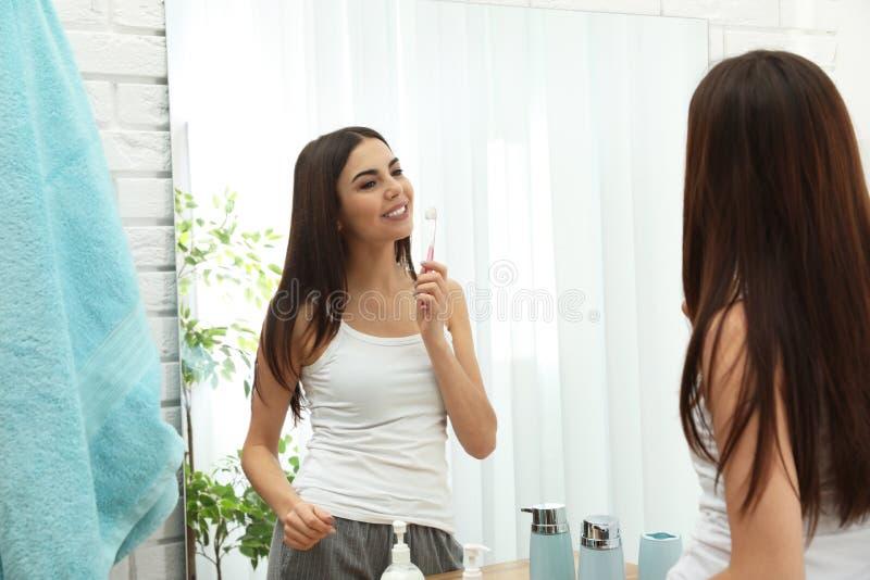 Dents de brossage de belle femme près de miroir dans la salle de bains photos libres de droits
