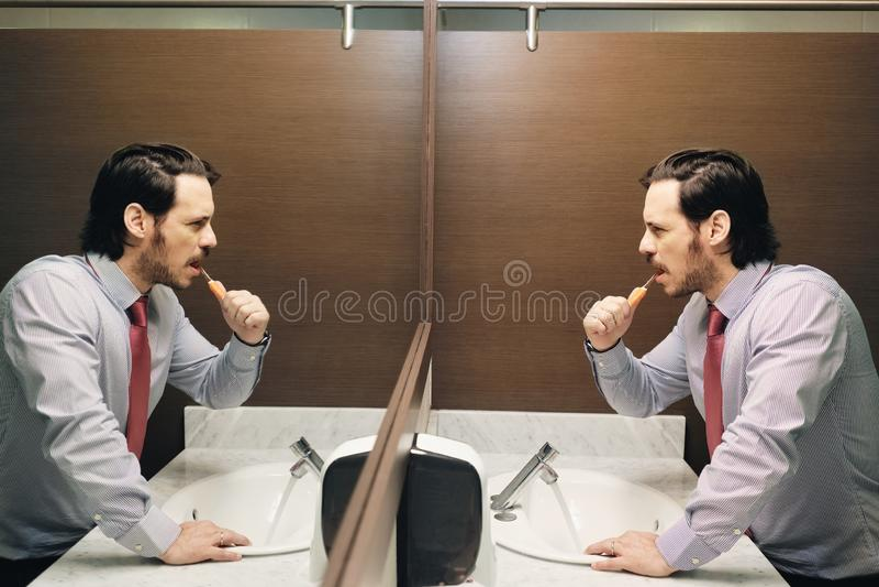 Dents de brossage d'homme d'affaires après pause de midi dans la salle de bains de bureau photos stock