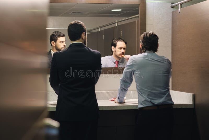 Dents de brossage d'homme d'affaires après pause de midi dans la salle de bains de bureau photo stock