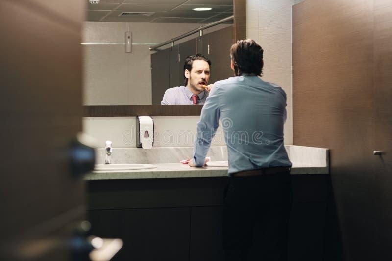 Dents de brossage d'homme d'affaires après pause de midi dans la salle de bains de bureau images stock