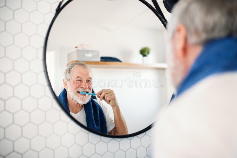 Dents de brossage d'un homme supérieur dans la salle de bains à l'intérieur à la maison Copiez l'espace image stock