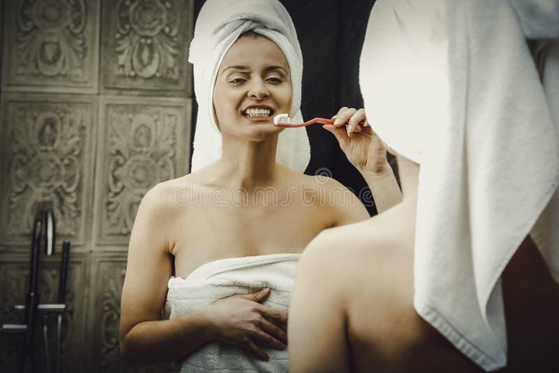 Dents de brossage de femme dans la salle de bains images stock