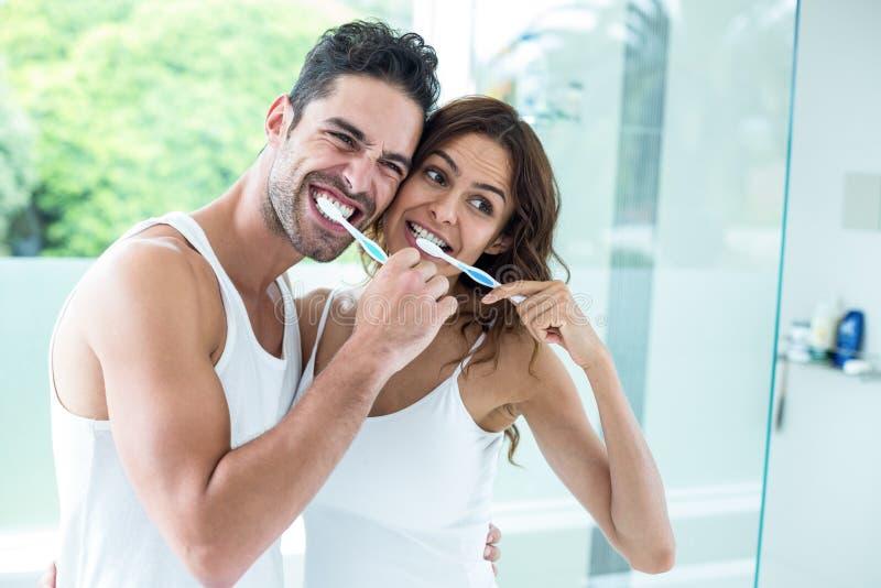 Dents de brossage de jeunes couples tout en se tenant dans la salle de bains image libre de droits