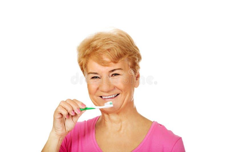 Dents de brossage de sourire de femme supérieure photographie stock
