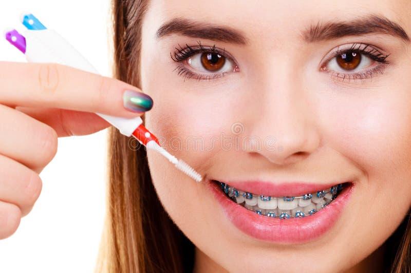 Dents de brossage de femme avec des accolades utilisant la brosse photo libre de droits