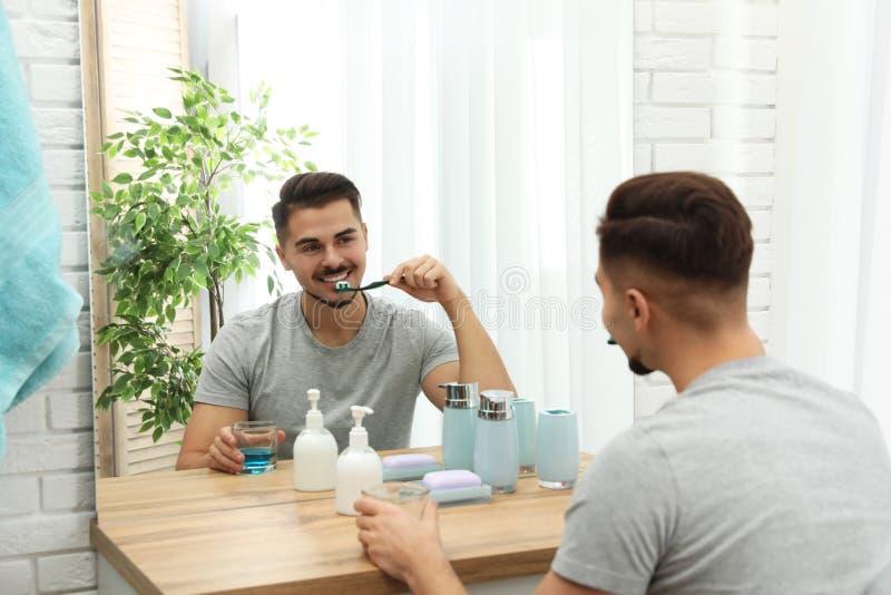 Dents de brossage de jeune homme près de miroir dans la salle de bains photographie stock