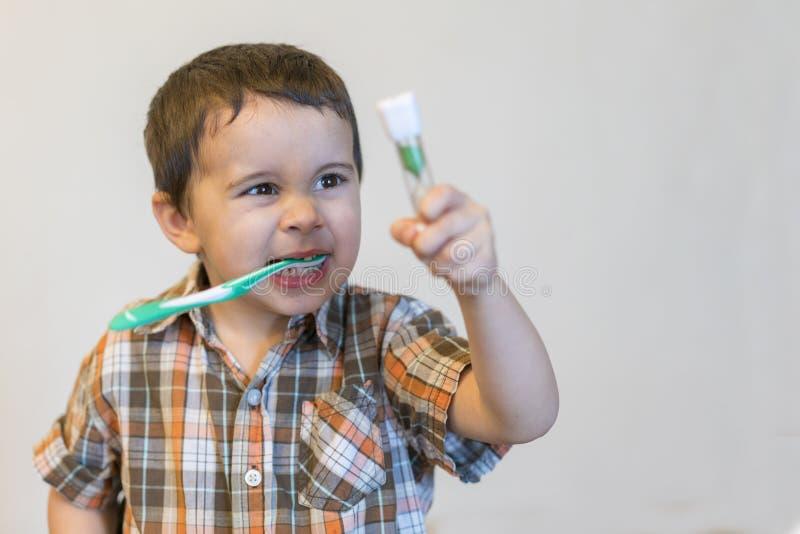 Dents de brossage de petit garçon de portrait dans la salle de bain, pyjamas de port d'enfant avec nettoyer ses dents pendant le  photos stock