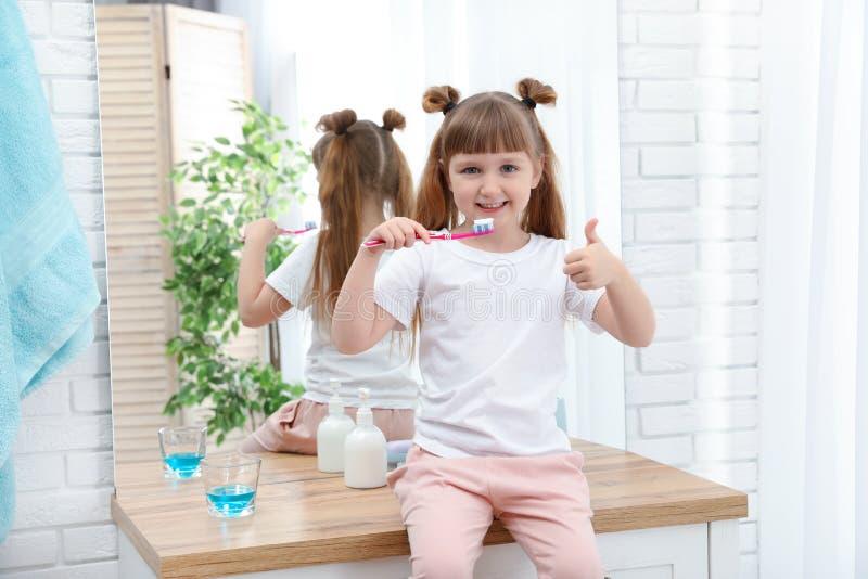 Dents de brossage de petite fille dans la salle de bains photographie stock libre de droits