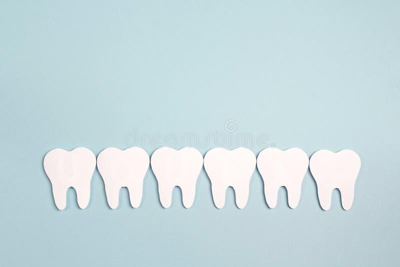 Dents de livre blanc sur le fond bleu Concept de jour de dentiste Configuration plate, vue supérieure, l'espace de copie pour le  photographie stock