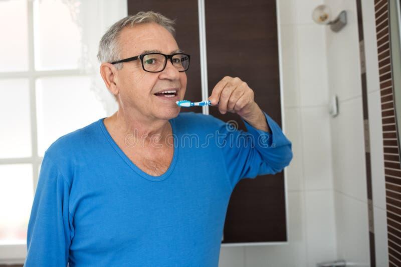 Dents de nettoyage d'homme supérieur avec la brosse à dents image stock