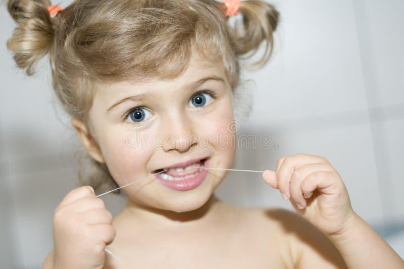dents de nettoyage de fille de soie dentaire photo libre de droits