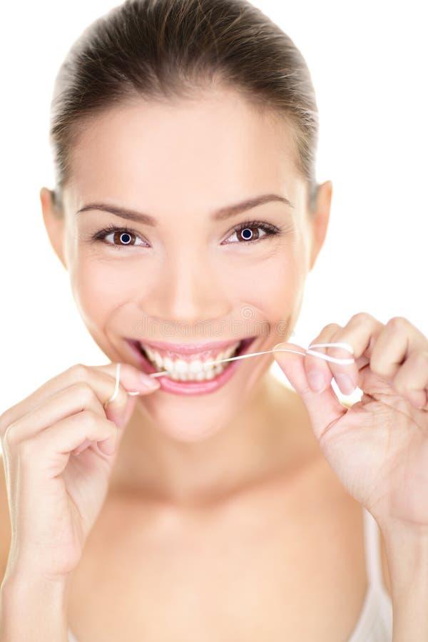 Dents flossing de femme souriant utilisant le fil dentaire photos stock