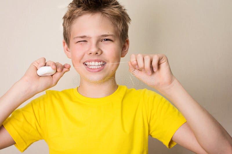 Dents flossing de garçon Portrait en gros plan de garçon de l'adolescence avec la Floride dentaire photo stock
