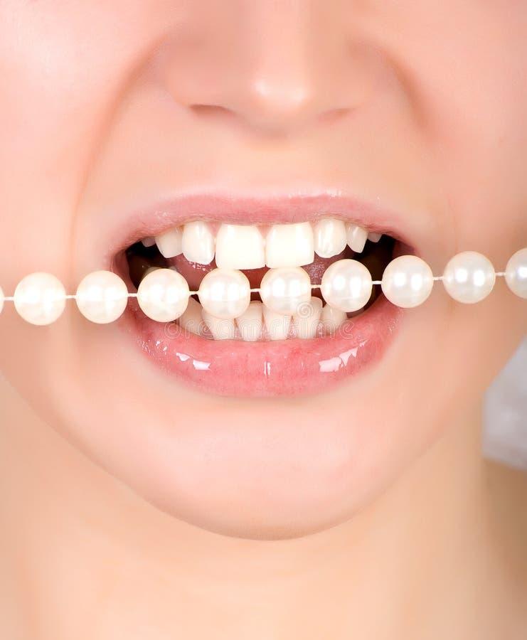 Dents mordant sur des perles de faux photo libre de droits