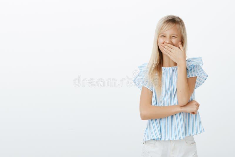 Dents perdues par fille heureuse après pomme acérée Enfant adorable joyeux positif avec les cheveux blonds, couvrant la bouche to photographie stock libre de droits