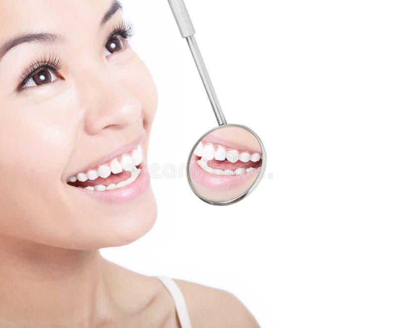 Dents saines de femme et un miroir de bouche de dentiste photos libres de droits
