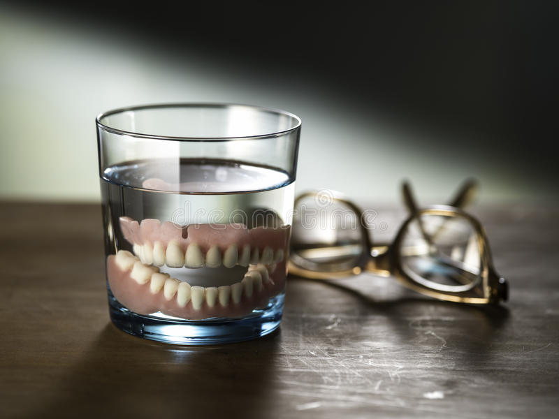 Dentures in a glass of water. Still life photography of dentures in a glass of water stock image