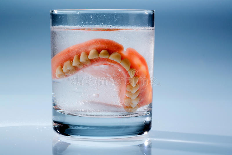 Dentures in water glass royalty free stock photography