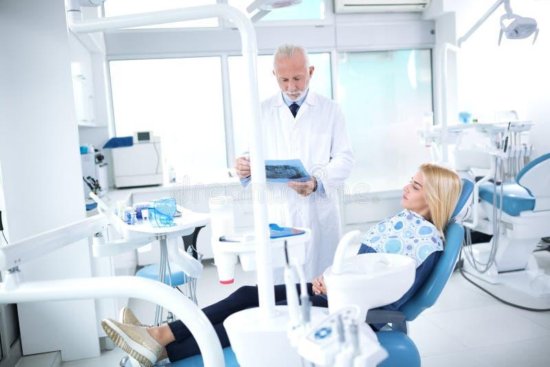 Dentystów spojrzenia przy promieniowaniem rentgenowskim cierpliwy ` s ząb fotografia stock