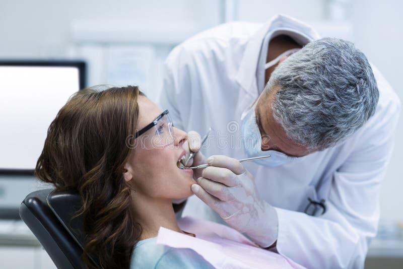 Dentysta egzamininuje żeńskiego pacjenta z narzędziami obraz stock