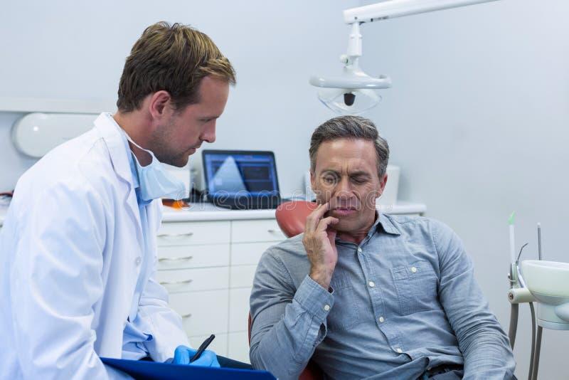 Dentysta egzamininuje męskiego pacjenta obraz stock