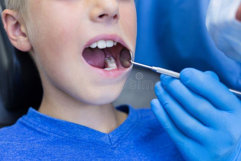 Dentysta egzamininuje młodego pacjenta z narzędziami obrazy stock
