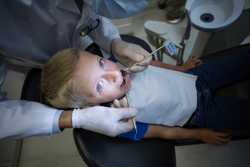 Dentysta egzamininuje młodego pacjenta z narzędziami fotografia stock