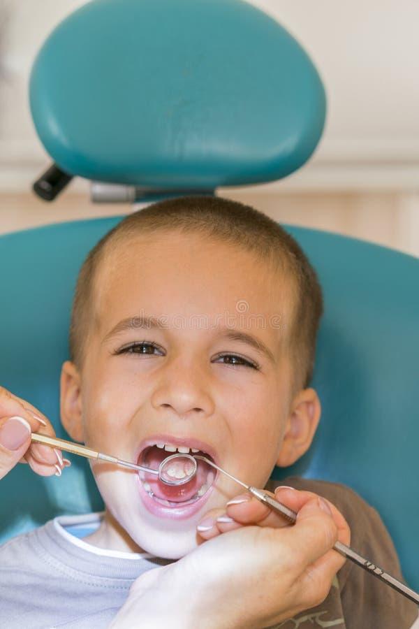 Dentysta egzamininuje małego boy& x27; s zęby w klinice Zamyka up chłopiec ma jego zęby egzamininujących dentysty A dzieckiem prz zdjęcie royalty free