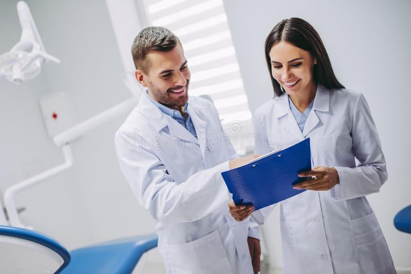 Dentysta i pomocniczy patrzeje schowek fotografia royalty free