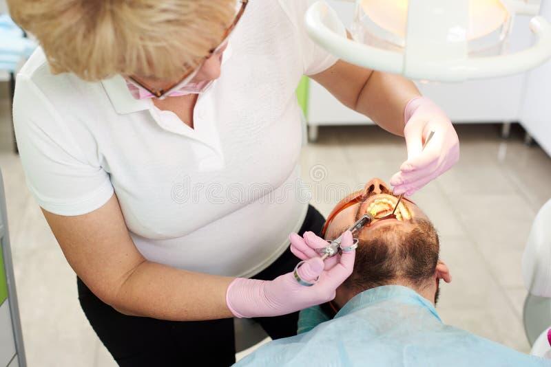 Dentysta kobieta robi znieczulać zastrzyka wśród cierpliwego ` s usta zdjęcia stock